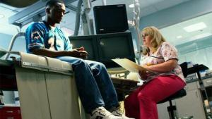 Adrian Doorbal (Anthony Mackey) consults flirty nurse Robin Peck (Rebel Wilson) in Pain & Gain