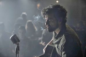 Llewyn (Oscar Isaac) takes to the stage in Inside Llewyn Davis