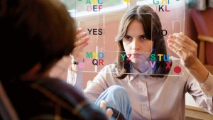 Jane (Felicity Jones) helps Stephen following the loss of his voice in The Theory Of Everything